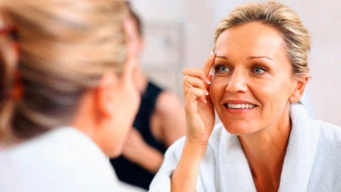 mujer mirandose a espejo rejuvenecimiento facial