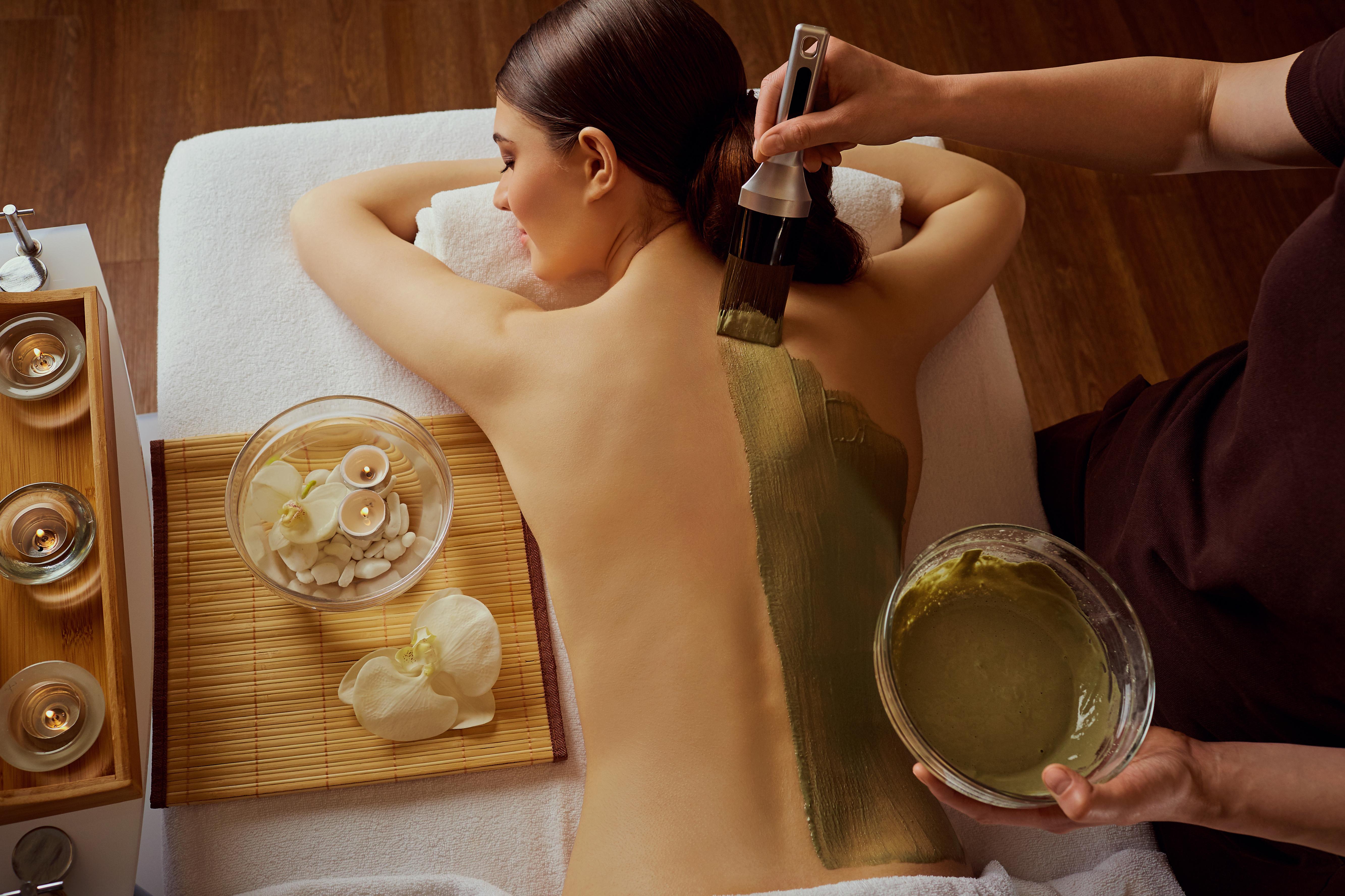 Mujer joven se pone una mascarilla de barro glacial en la espalda en el Spa en casa