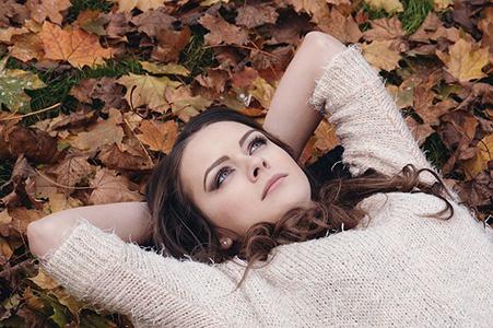 foto chica con belleza natural encima hojas otoño